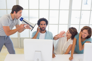 Man yelling through a megaphone at business people in the office